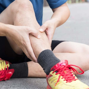 Runner sitting down holding his leg in pain.
