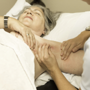 Woman lying on a bed receiving treatment for her arm lymphedema